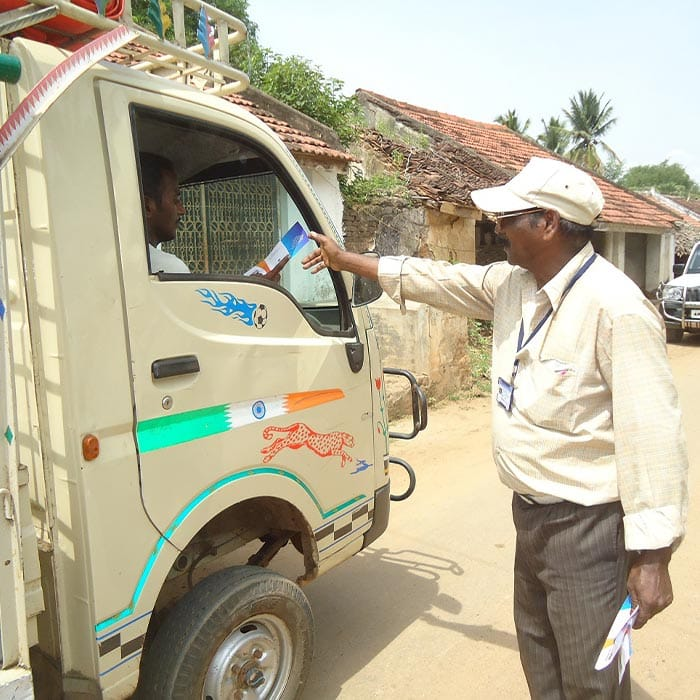 local pastor handing out ccm tracts in india to a truck driver
